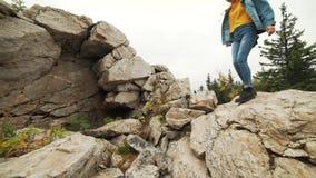 Młoda kobieta wycieczkuje up halnego skłon jest ubranym rzemiennego mountaineering inicjuje Wycieczkowicz dziewczyna na halny tre zbiory