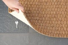 Młoda kobieta wyjawia chującego klucz pod drzwiową matą, odgórny widok obraz stock