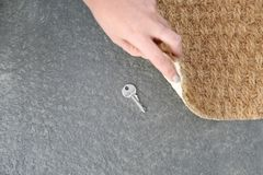 Młoda kobieta wyjawia chującego klucz pod drzwiową matą, odgórny widok zdjęcia stock