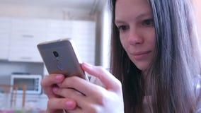 Młoda kobieta wyszukuje internet strony na kuchni w domu czyta na smartphone zbiory