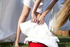 Młoda kobieta z basenem czysta pościel wieszał w górę prześcieradeł na clothesline fotografia royalty free