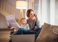 Młoda kobieta z berbeć córką siedzi indoors, pracujący w domu obraz stock