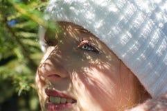 Młoda kobieta z białym kapeluszem i niebieskie oczy za drzewnym branche Zdjęcie Stock