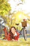Młoda kobieta z bicyklem w parku na słonecznym dniu Zdjęcia Royalty Free