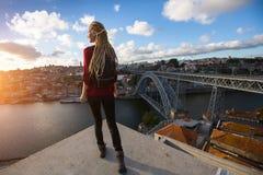 Młoda kobieta z blond dreadlocks spotyka zmierzch na viewing platformie naprzeciw Dom Luis Ja most przez rzekę Obraz Royalty Free