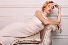 Młoda kobieta z blondynem w retro stylu, jest ubranym elegancką biel suknię Obrazy Royalty Free