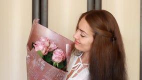 Młoda kobieta z bukietem róże uśmiecha się woń i obwąchuje zbiory