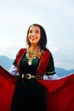 Młoda kobieta z ciemnym włosy, zieleń, czerwieni złoto i suknia, aksamitny dziejowy klejnot i subtelny uśmiech i obraz stock