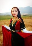 Młoda kobieta z ciemnym włosy, zieleń, czerwieni złoto i suknia, aksamitny dziejowy klejnot i subtelny uśmiech i obraz royalty free