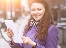 Młoda kobieta z cyfrową pastylką na zamazanym miasta tle obraz stock