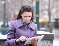Młoda kobieta z cyfrową pastylką na zamazanym miasta tle fotografia royalty free