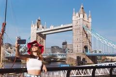 Młoda kobieta z czerwonym kapeluszowym bierze selfie w Londyn z wierza mostem na tle zdjęcia stock