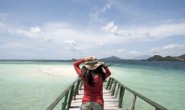 Młoda Kobieta z czerwonym koszulowym mienie kapeluszem przy plażą dla wakacje fotografia stock