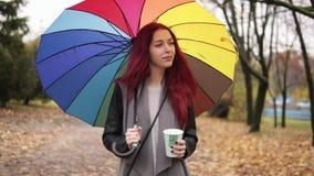 Młoda kobieta z czerwonym włosianym odprowadzeniem w jesieni parkowej i pije kawę od papierowej filiżanki podczas gdy trzymający  zdjęcie wideo
