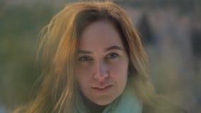 Młoda kobieta z czerwonym włosy i błękitnym szalikiem patrzeje prostą i uśmiechniętą zbiory wideo
