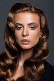 Młoda kobieta z długą glansowaną kędzierzawą fryzurą Obraz Royalty Free