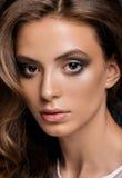 Młoda kobieta z długą glansowaną kędzierzawą fryzurą Obraz Stock