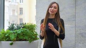 Młoda kobieta z długie włosy śmiać się i aktywnie gestykulować podczas stoi w górę rozmowy zdjęcie wideo