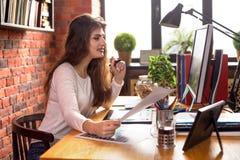 Młoda kobieta z długie włosy działaniem w loft stylu biurze lub w domu Ona trzyma ono uśmiecha się i papier Filiżanka kawy lub zdjęcia royalty free