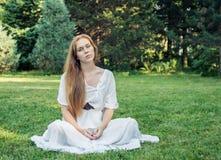 Młoda kobieta z długie włosy obsiadaniem na trawie w parku fotografia stock