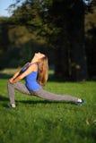 Młoda kobieta z długie włosy robić lunge z jego kierowniczym rzucającym b Fotografia Royalty Free