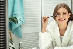 Młoda kobieta z długimi rzęsami i szczotkarskim pobliskim lustrem obrazy stock