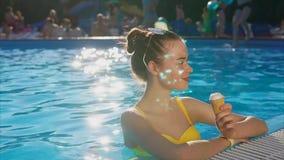 Młoda kobieta z dobrym nastrojem i śliczny cieszymy się lody w basenie zdjęcie wideo