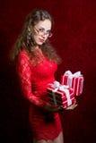 Młoda kobieta z dwa paskował prezentów pudełek gapienia w kamerę Zdjęcia Stock