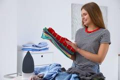 Młoda kobieta z fałdowymi ubraniami zbliża prasowanie deskę zdjęcie stock