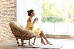 Młoda kobieta z filiżanką aromatyczny kawowy obsiadanie zdjęcie stock