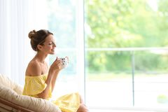 Młoda kobieta z filiżanką aromatyczny kawowy obsiadanie zdjęcia stock