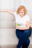 Młoda kobieta z filiżanką kawy na kanapie Obrazy Royalty Free