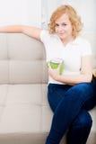 Młoda kobieta z filiżanką kawy na kanapie zdjęcie stock