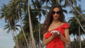 Młoda kobieta z frangipani kwitnie blisko drzewek palmowych Ona cieszy się ich woń zdjęcie wideo