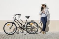 Młoda kobieta z gadżetem i rowerem Fotografia Royalty Free