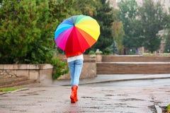 Młoda kobieta z jaskrawym parasolem fotografia stock