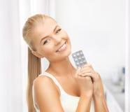 Młoda kobieta z jeden paczką pigułki Zdjęcie Royalty Free