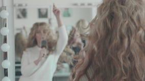 Młoda kobieta z kędzierzawym włosy błaź się przed lustrem i śpiewa zdjęcie wideo