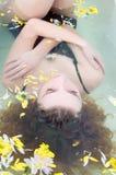 Młoda kobieta z kędzierzawym włosy bierze skąpanie z ziele obraz royalty free