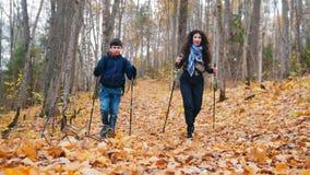 Młoda kobieta z kędzierzawym włosy i chłopiec na scandinavian spacerze Sezon Jesienny zbiory