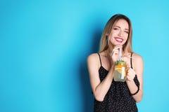 Młoda kobieta z kamieniarza słojem smakowita lemoniada na koloru tle Naturalny detox napój obraz royalty free