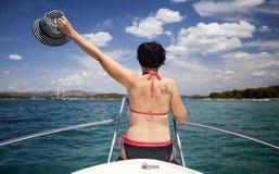 Młoda kobieta z kapeluszowym obsiadaniem na przodzie żagiel łódź Fotografia Royalty Free