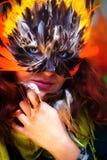 Młoda kobieta z kolorową piórkową karnawałową twarzy maską na jaskrawym kolorowym tle, kontakt wzrokowy, uzupełniał artysty obrazy stock