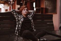 Młoda kobieta z krótkim czerwonym włosy w barze stawia ona nogi na ławce obraz stock