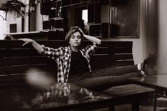 Młoda kobieta z krótkim włosy w barze stawia ona nogi na stole fotografia stock
