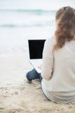 Młoda kobieta z laptopem na zimno plaży. tylni widok zdjęcie stock