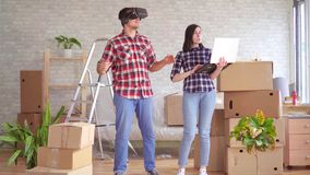 Młoda kobieta z laptopem pokazuje mężczyźnie w VR szkłach projekt nowy mieszkanie zdjęcie wideo