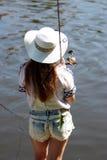 Młoda kobieta z lat dungarees i flancami podczas gdy łowiący Zdjęcie Royalty Free