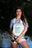 Młoda kobieta z lat dungarees i flancami podczas gdy łowiący Zdjęcie Stock