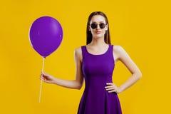 Młoda kobieta z lotniczym balonem nad żółtym tłem zdjęcia royalty free